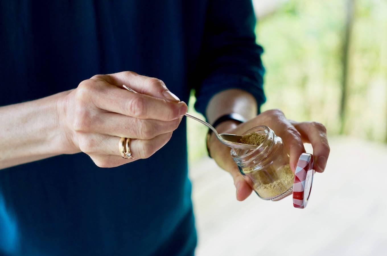 Hand mit Löffel und Gewürz